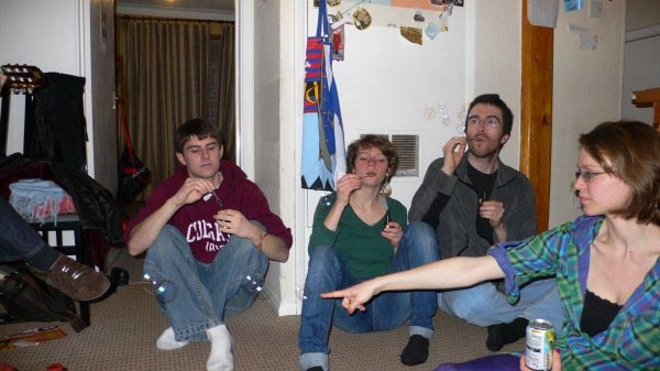 College students blowing bubbles while sitting on the floor.