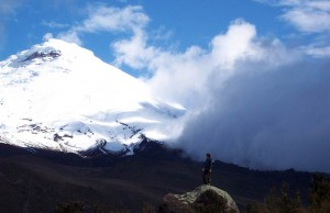 Volcanology student standing on a boulder looking up at Cotopaxi volcano in Ecuador