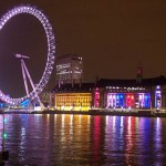 The London Eye lit up across the Thames at night.