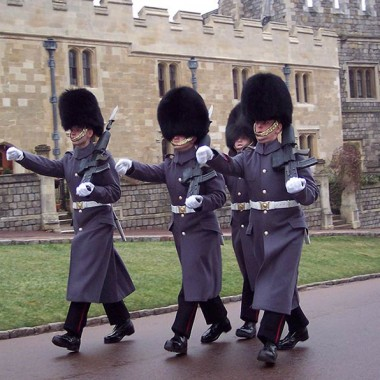 Guards at Windsor Castle march in gray uniforms and funny bear hats