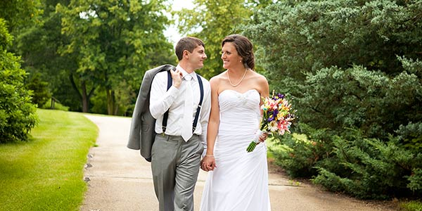 Katie and Jason Kammerdiener walking in Klehm Arboretum on their wedding day