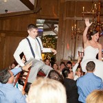 Wedding guests lift bride and groom during the Hava Nagila