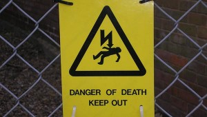 """Sign showing a horizontal body with a lightning-like arrow pointing at it, reading """"Danger of Death: Keep Out"""""""