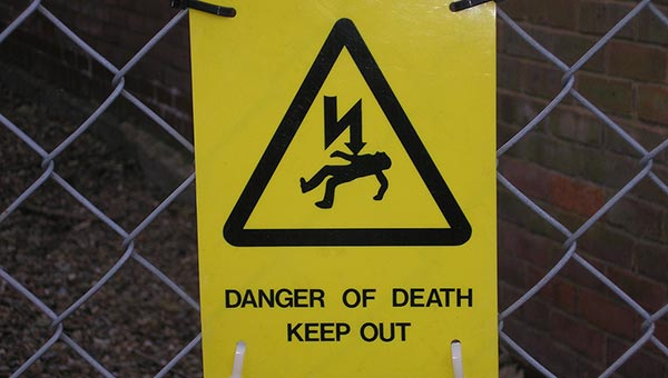 "Sign showing a horizontal body with a lightning-like arrow pointing at it, reading ""Danger of Death: Keep Out"""