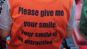 """Child's t-shirt reads """"Please give me your smile. Your smile is so attractive."""""""
