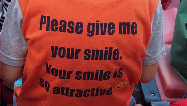 "Child's t-shirt reads ""Please give me your smile. Your smile is so attractive."""