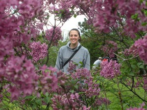 Katie smiles through a frame of lilacs