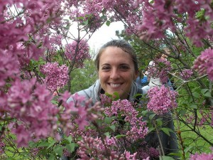 Katie smiles through a frame of lilacs
