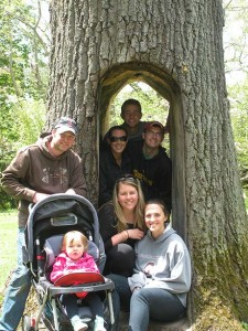 Katie, Shawn, Addy, Sarah, Leah, Jason, and Adam post for a photo in a carved-out tree