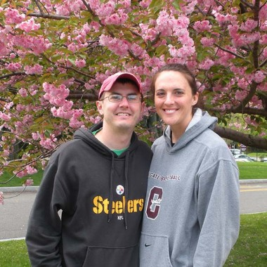 Katie and Jason pose for a photo under a flowering tree