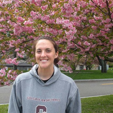 Katie smiles under a flowering tree
