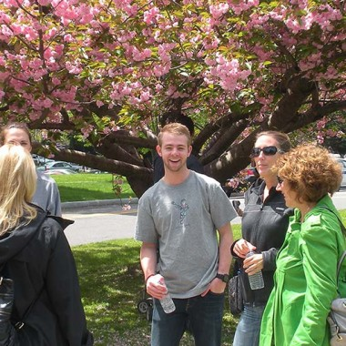 Family members talk under a flowering tree at the Lilac Festival