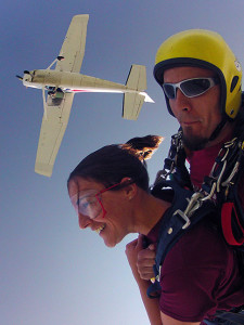 Katie and instructor in free fall with plane visible above